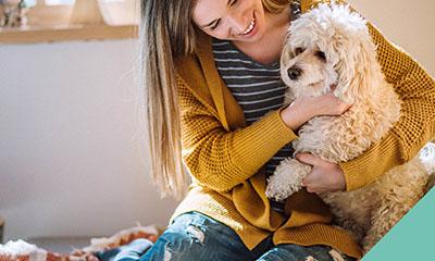 A lady cuddling a dog on her lap